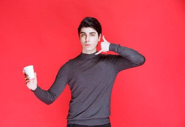 Uomo che tiene una tazza di caffè e che fa segno a una chiamata