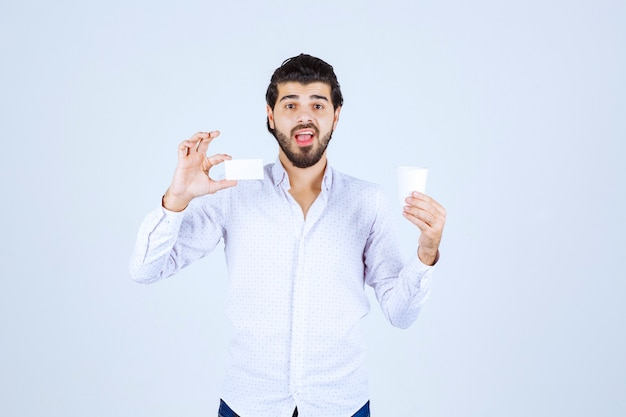 Man holding a coffee cup in one hand and presenting his business card in another hand