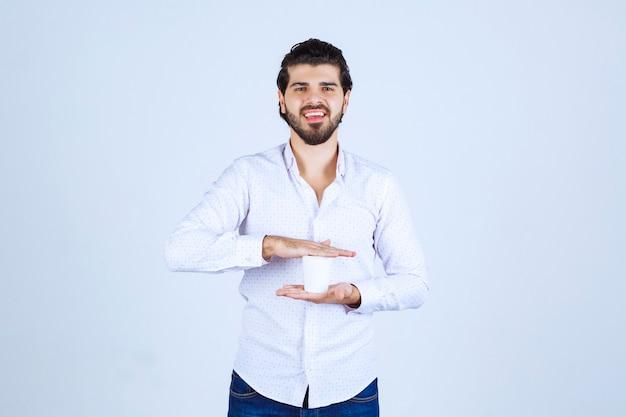 Uomo che tiene la tazza di caffè tra due mani