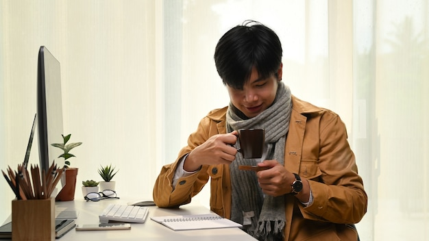 Man holding coffee cup with enjoyment coffee time in home office.
