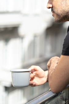 Man holding coffee or tea cup standing on balcony