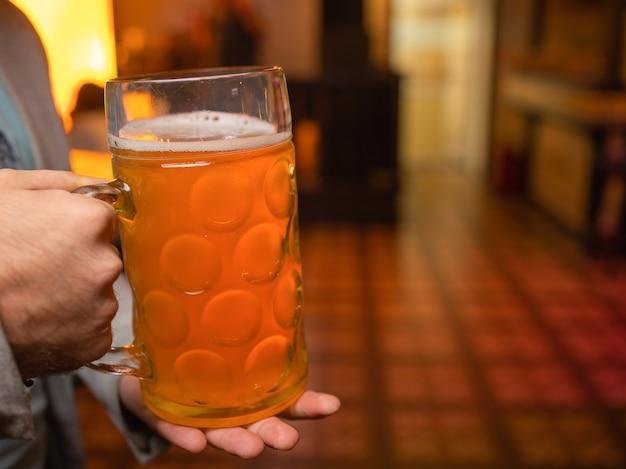 手で冷たいビアグラスを持っている男。 refresmentコールドラガービール。