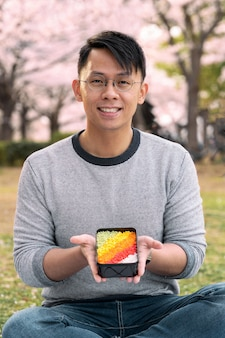 Man holding a colorful dessert