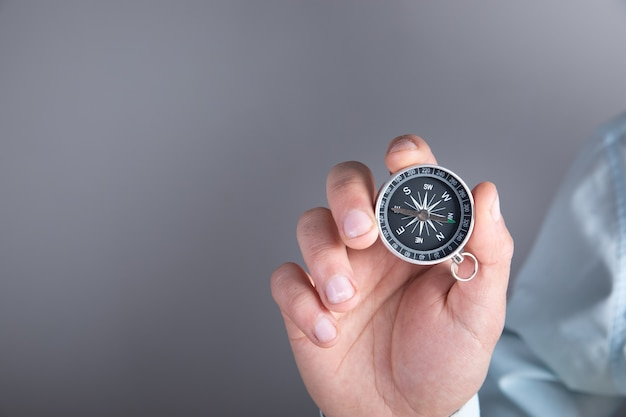 Man holding a compass in his hand on a gray surface