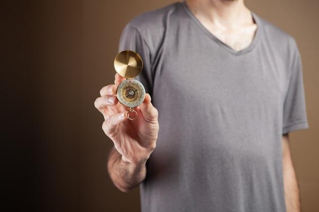 Человек, держащий компас на коричневом фоне