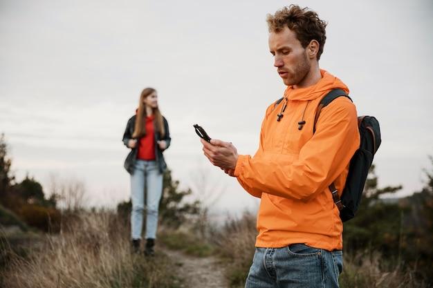 Мужчина держит компас во время поездки с подругой