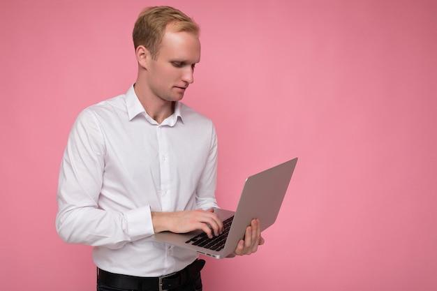 핑크 벽 위에 절연 모니터를보고 흰 셔츠를 입고 키보드에 입력하는 컴퓨터 노트북을 들고 남자.