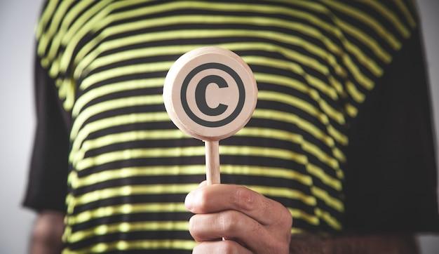 Мужчина держит символ авторского права. авторское право. интеллектуальная собственность