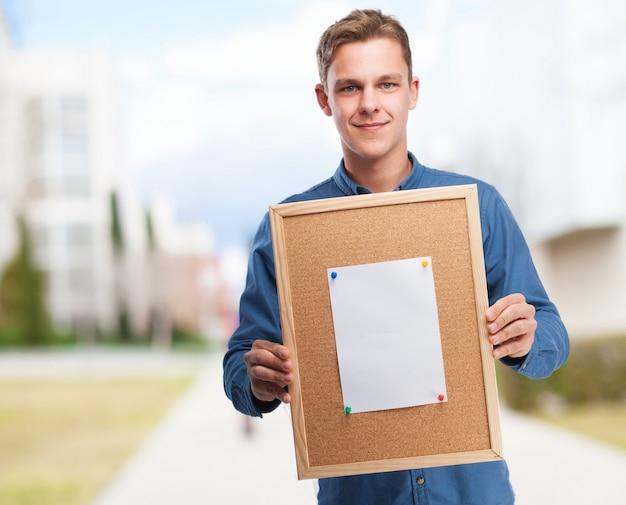 Man holding a cork board
