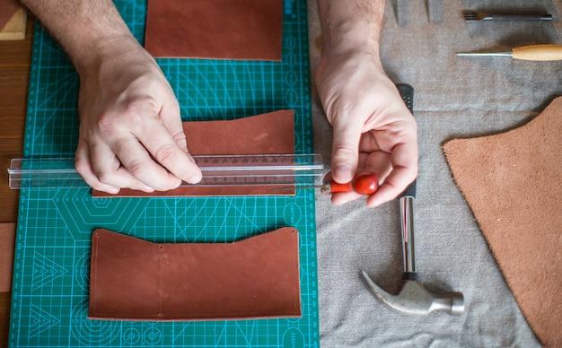 Человек, держащий инструмент крафта и работает на кусок кожи