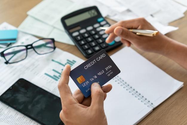 クレジットカードを保持し、電卓、アカウント、保存の概念を使用している人。 Premium写真