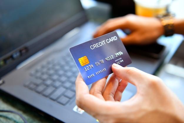 신용 카드를 들고 온라인 쇼핑을 위해 노트북을 사용하는 남자