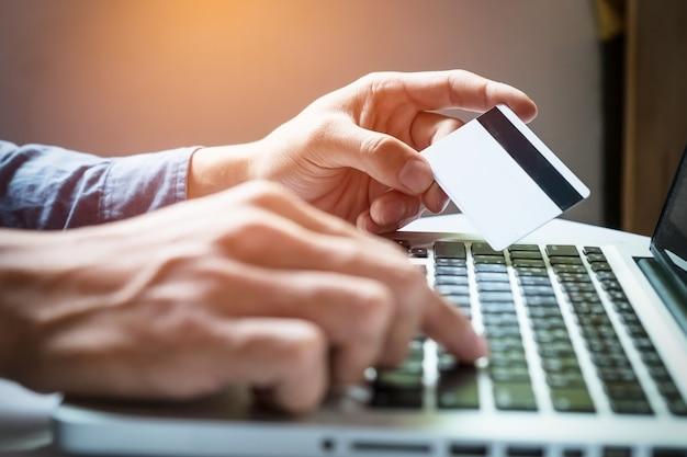 Man holding carta di credito in mano e l'immissione di codice di sicurezza utilizzando la tastiera del computer portatile