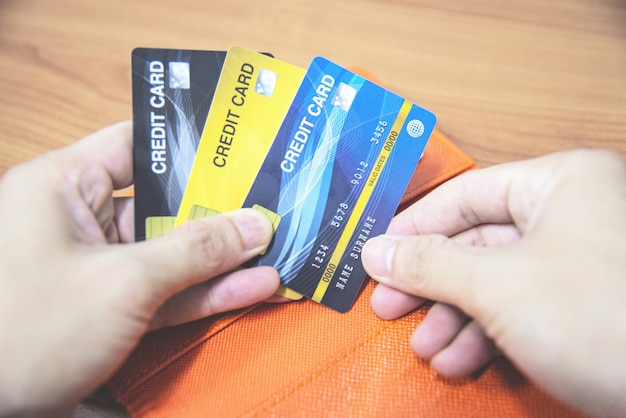 Man holding credit card in hand - online paying from home or increased liabilities debt credit card concept
