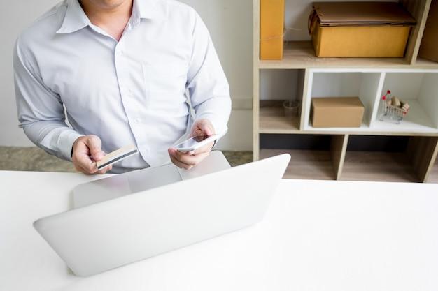 Мужчина держит кредитную карту в руке и вводит код безопасности с помощью смартфона на клавиатуре ноутбука, концепция онлайн-покупок
