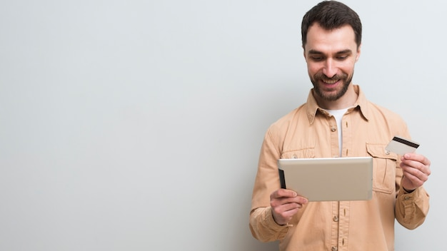 Man holding credit card and tablet with copy space
