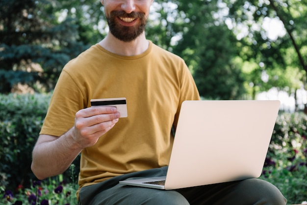 Man holding credit card, using laptop, online shopping. freelancer receive payment