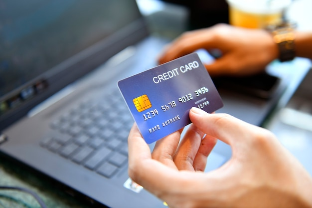 Man holding credit card and using laptop for online shopping