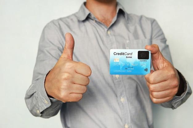 Мужчина держит кредитную карту со встроенным сканером отпечатков пальцев и показывает палец вверх. концепция безопасной оплаты без пин-кода. биометрический банкинг. человек доволен использованием новых технологий. сенсорный датчик.