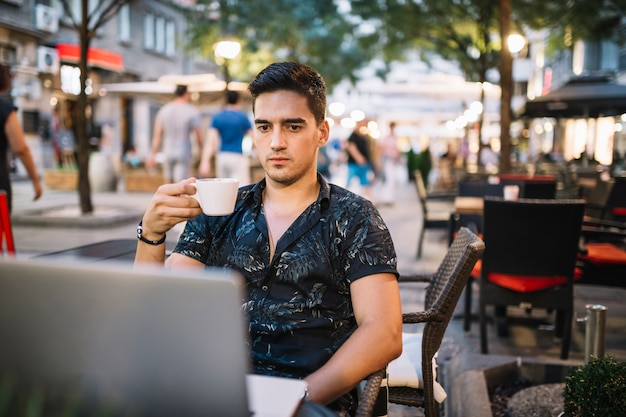 Man holding cup of coffee looking at laptop screen