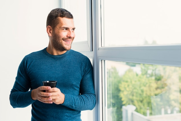 Man holding a cup of coffee and looking through the window