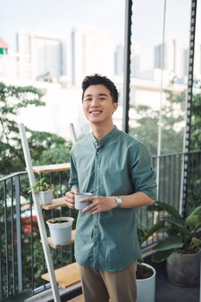 Man holding cup of coffee and smiling on balcony