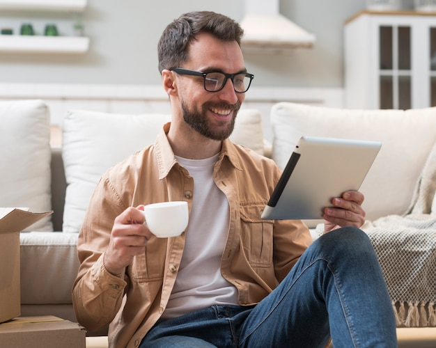 Man holding cup of coffee while looking at tablet