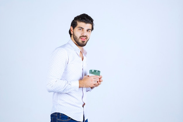 Man holding a cup of drink and feeling satisfied