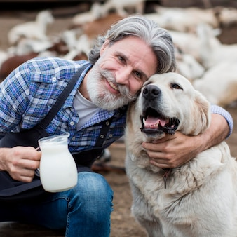 Man holding cup of goat milk while playing with dog