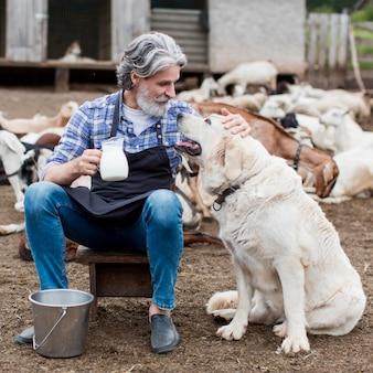 山羊乳のカップを保持していると犬と遊ぶ男