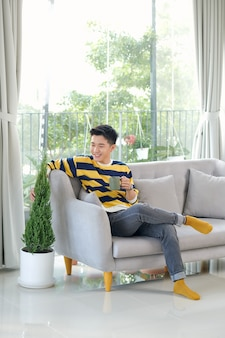 Man holding a cup of tea in his living room