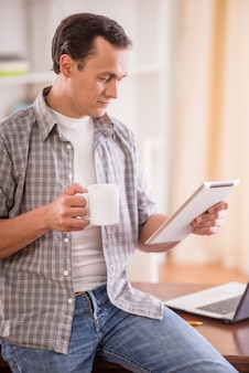 Man holding a cup of tea and reading digital tablet.