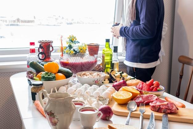 Мужчина держит чашку со многими продуктами, овощами, фруктами, готовится к обеду