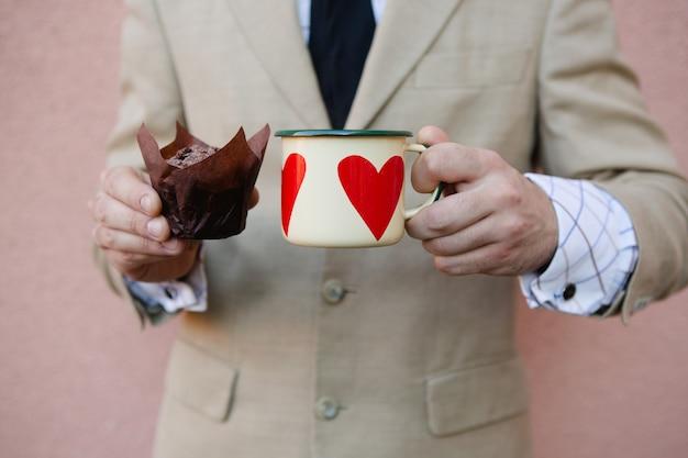 心でカップケーキとコーヒーのホットカップを保持している男