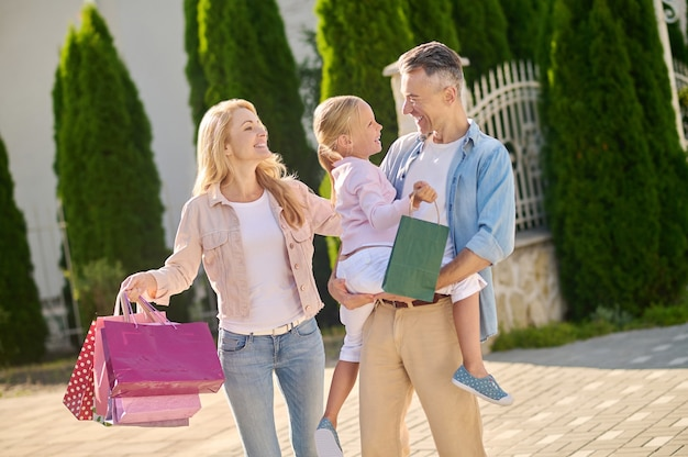 Man holding daughter and woman with bags