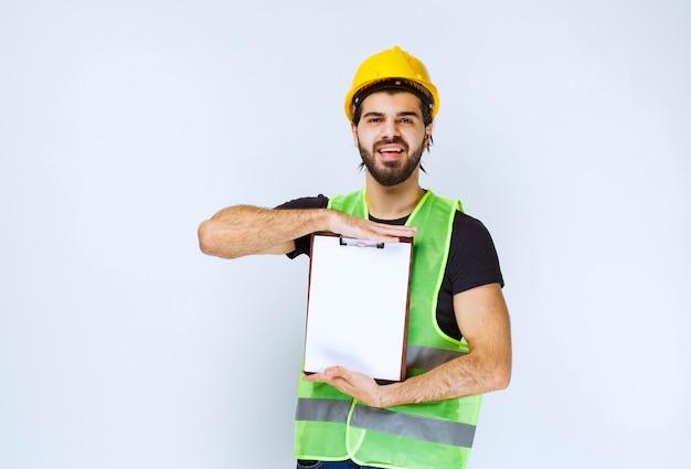 Uomo che tiene e dimostra la versione finale del progetto di costruzione.
