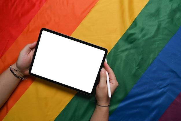 Человек, держащий цифровой планшет над красочным радужным флагом. лгбт.