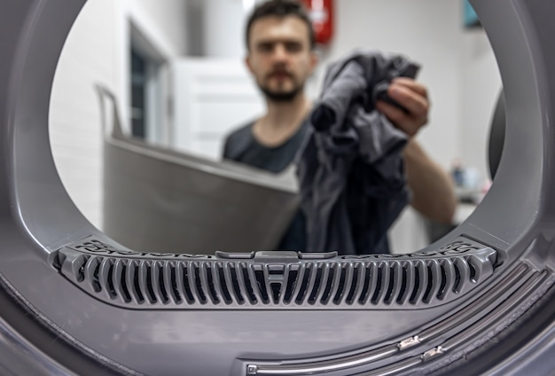 Man holding dirty cloth in hand view inside of washing machine.