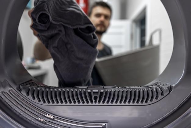 汚れた布を手に持った男が洗濯機の内部を眺めています。