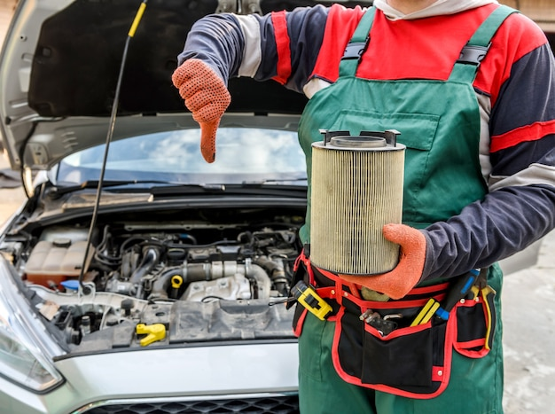 Man holding dirty filter near car at workshop
