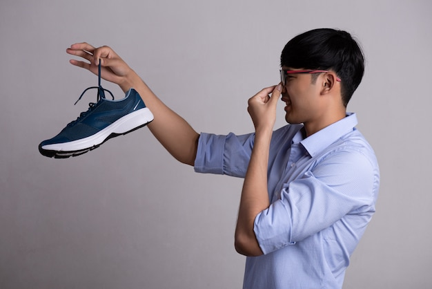 Man holding dirty stinky shoe with an expression of disgust.
