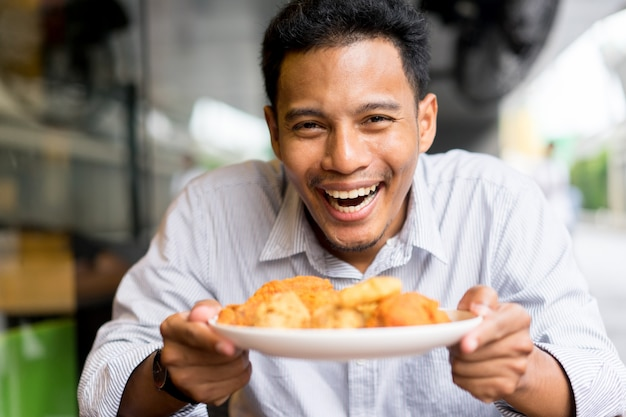 Man holding dish of fried chicken with happy