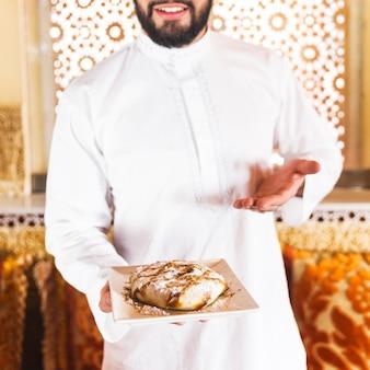 Мужчина, держащий блюдо из арабской пищи