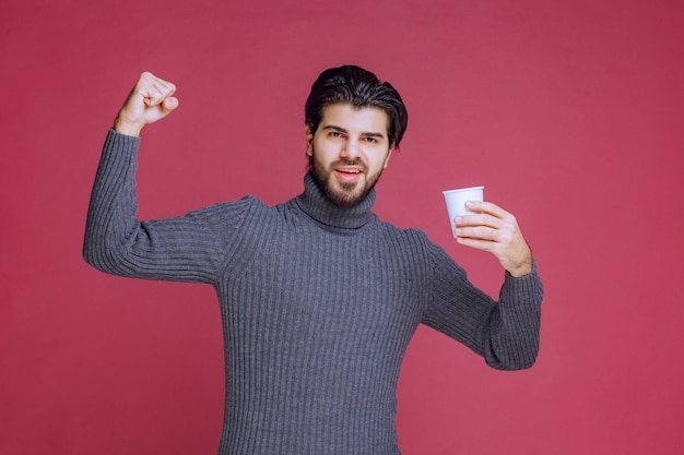 Man holding a disposable coffee cup, feeling powerful and energic.