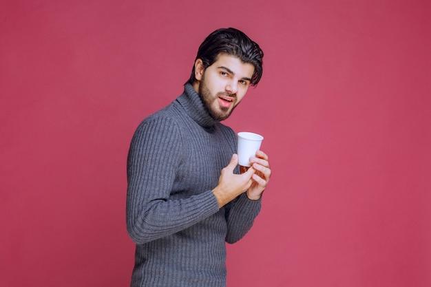 L'uomo tiene in mano una tazza di caffè usa e getta e si sente positivo.