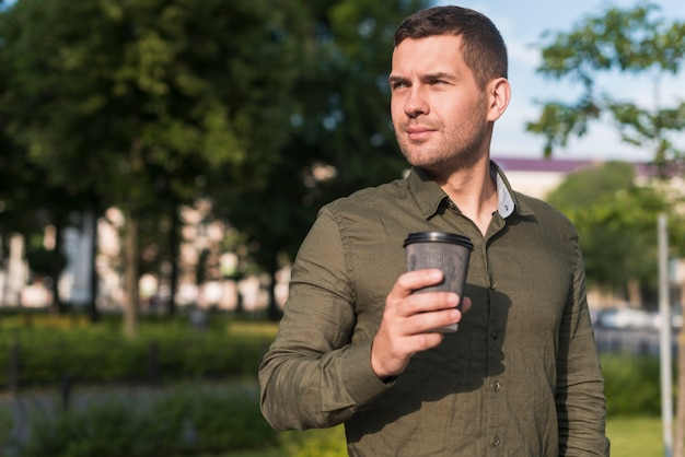 Man holding disposable coffee cup looking away at park