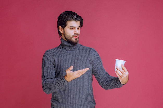 Man holding a disposable coffee cup and pointing at it.