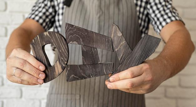 Uomo che tiene lettere fai da te in legno