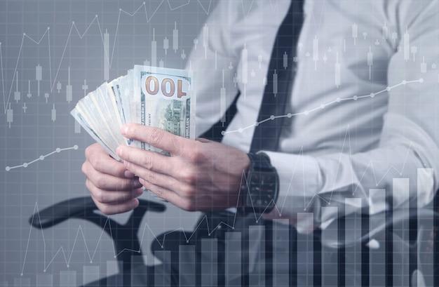 成長グラフでドル紙幣を保持している男。