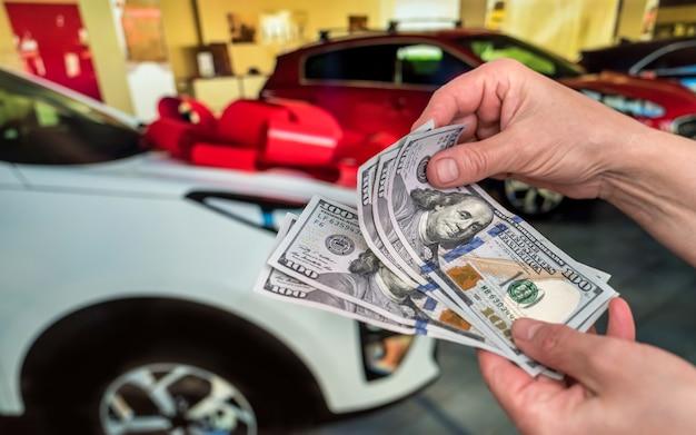 임대 달러를 들고 남자 또는 배경으로 차를 구입. 비즈니스 개념